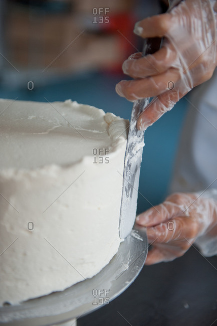 A woman frosts a cake