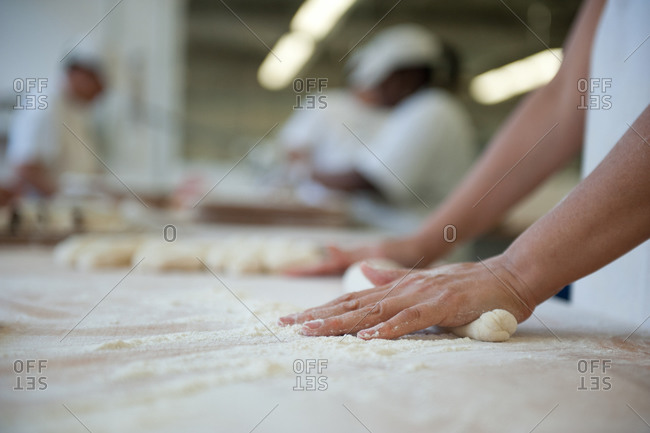 A woman shaping bread dough in a bakery