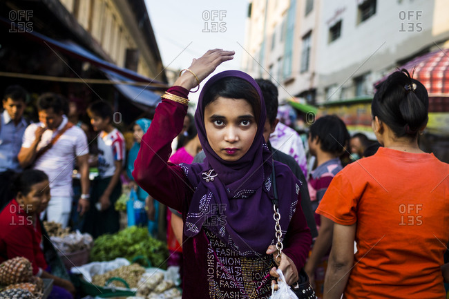 Yangon, Myanmar - January 28, 2015: A young Burmese woman walks through a street market in downtown