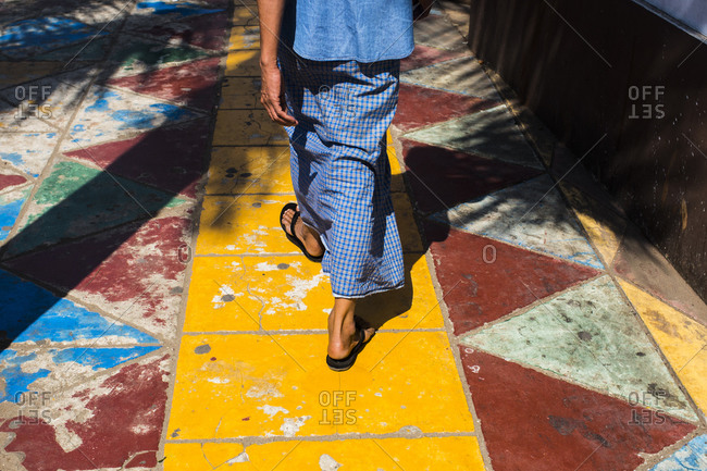 A young Burmese man walks along a yellow foot path in downtown Yangon, Myanmar