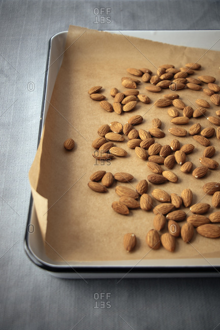 Almonds on parchment paper on a roasting pan
