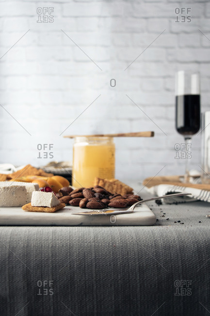 Side view of a cheese plate with wine, nuts, fruit and honey