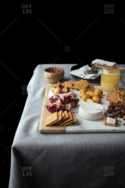Platter of cheese, fruit, nuts, crackers and honey on a table's edge