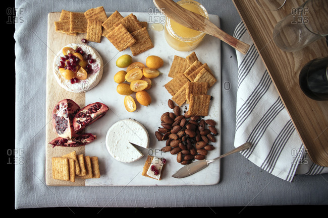 Overhead view of a cheese plate with wine, nuts, fruit and honey
