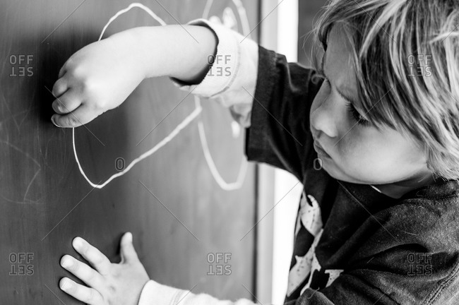 Young boy drawing on a blackboard