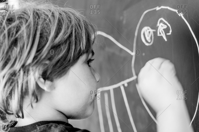 Young boy drawing on a chalkboard