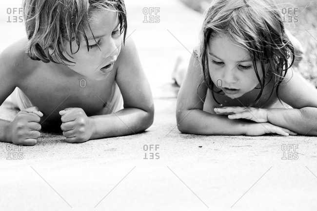 Young boy and girl exploring sidewalk