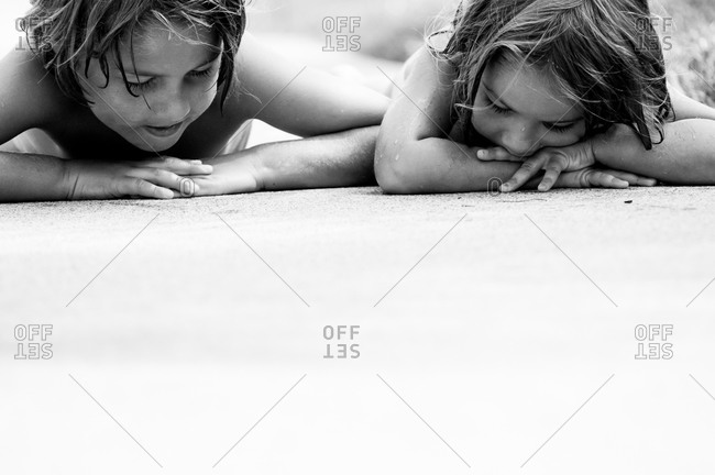 Young boy and girl looking at sidewalk