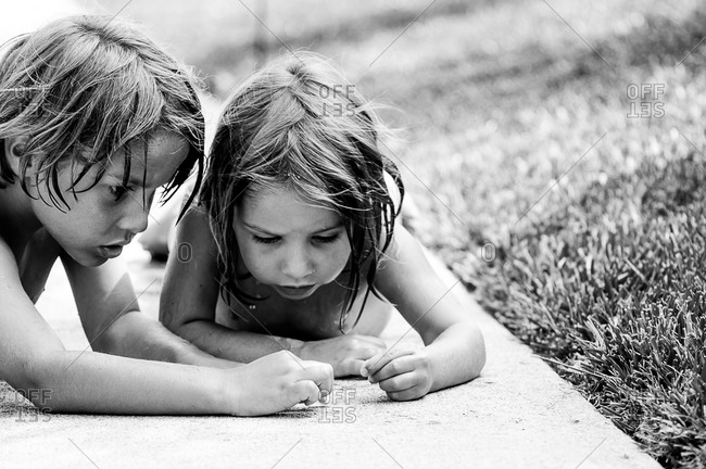 Young boy and girl checking out sidewalk