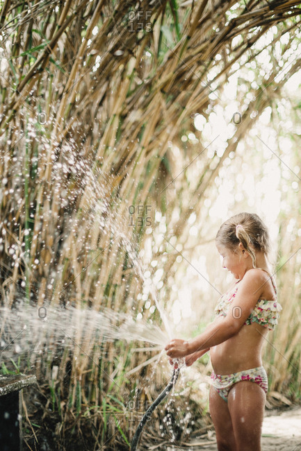 A little girl plays with a hose