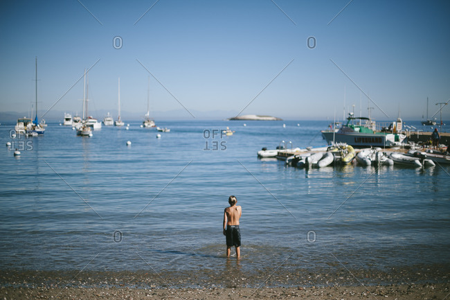 Boy standing in ocean water watching boats