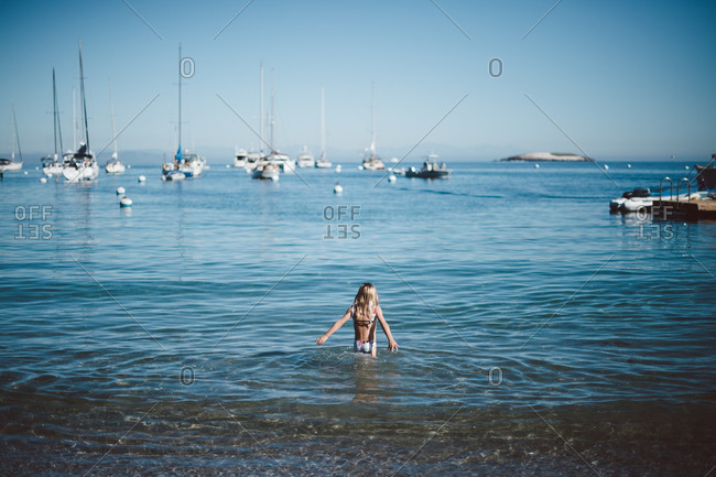 Girl standing in ocean water looking out to sea