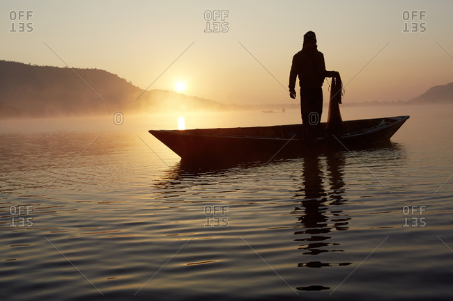 A fisherman on a small canoe on a lake in Pokhara, Nepal