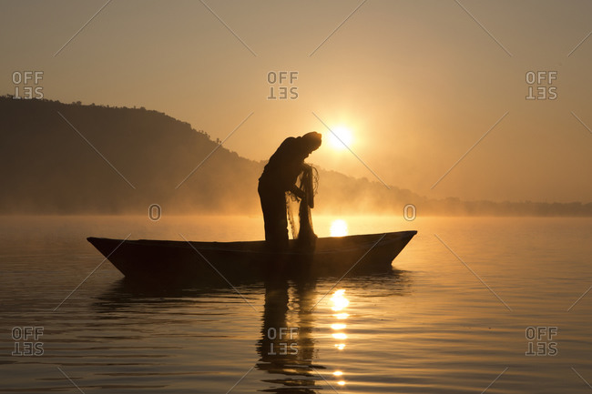 A fisherman pulling in his net on a lake in Pokhara, Nepal