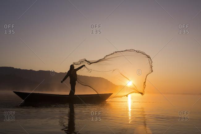 A fisherman casts a net on a lake in Pokhara, Nepal