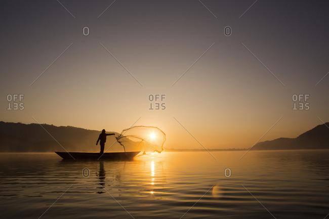 A man casts a net on a lake in Pokhara, Nepal