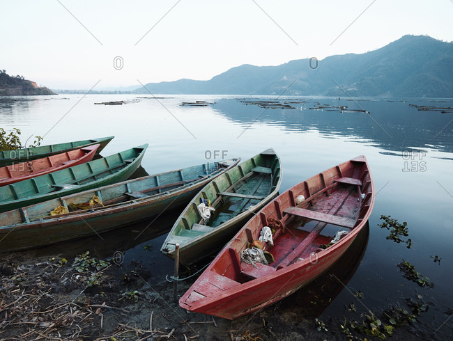 Fishing boats on the shore of a lake in Pokhara, Nepal