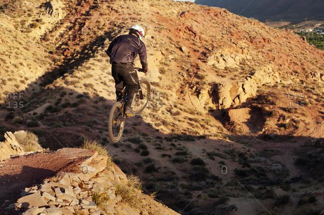 Man riding his bike off a rock