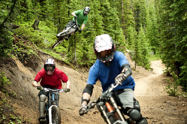 Downhill mountain bikers racing on a trail
