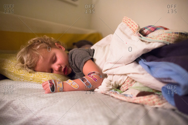 Sleeping boy with bandages all over his arm