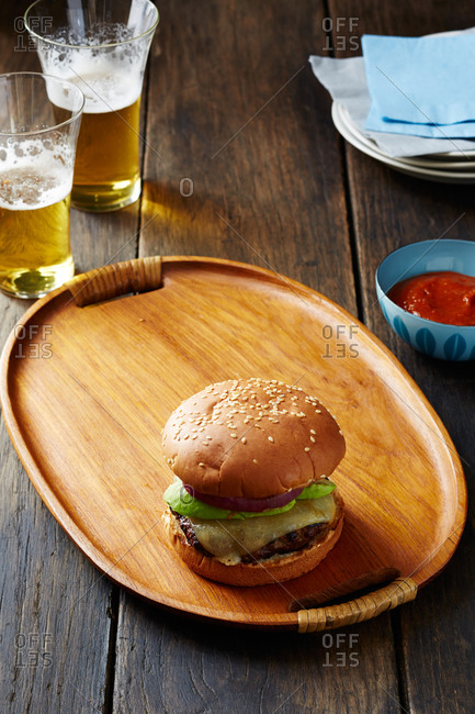Cheeseburger on a wooden plate with avocado and onion