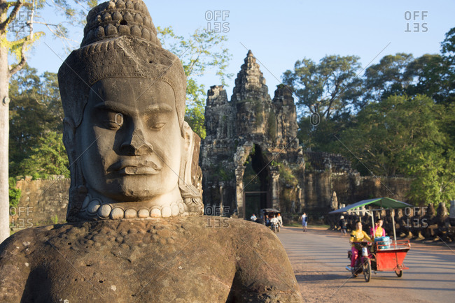 Statue and bike taxis at Angkor archeological complex