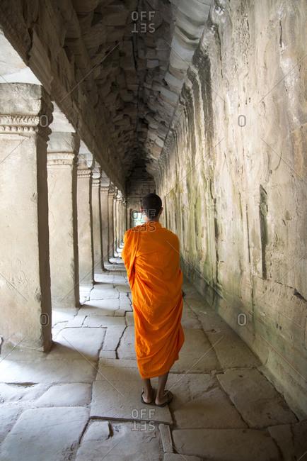 Monk wandering Angkor archeological complex