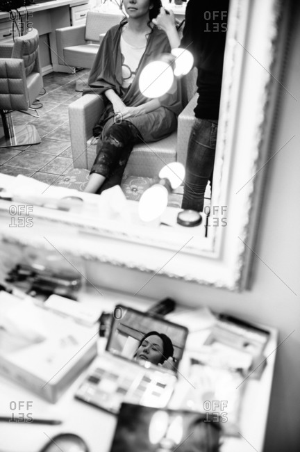 Bride in mirror getting makeup done