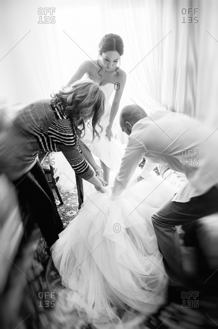 Bride getting helped into dress