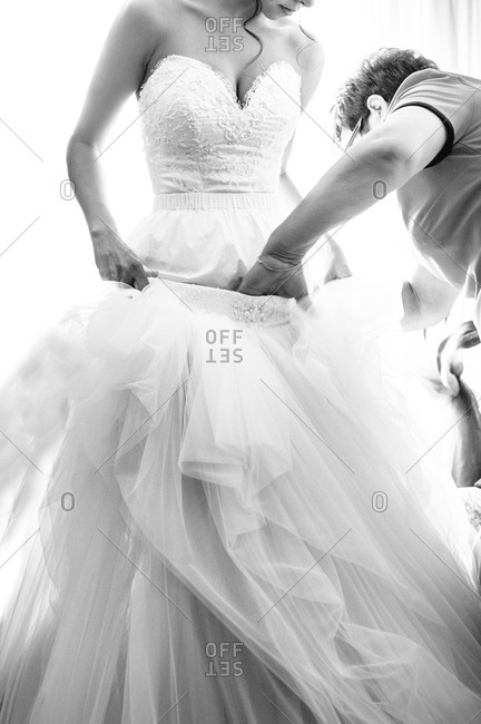 Bride having help with bridal gown