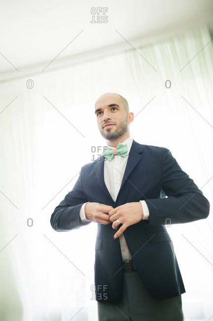 Groom putting on suit and bowtie