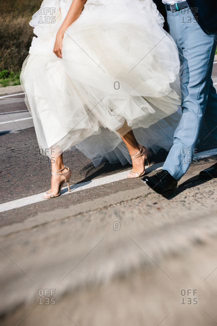 Feet of bride and groom running outside