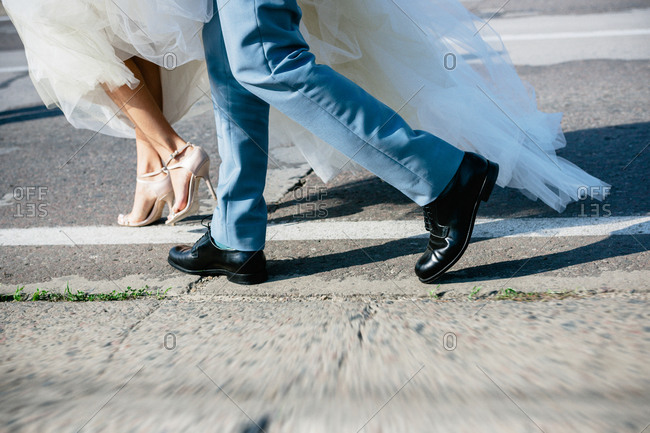 Feet of bride and groom running outdoors