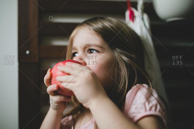 A little girl eats an apple