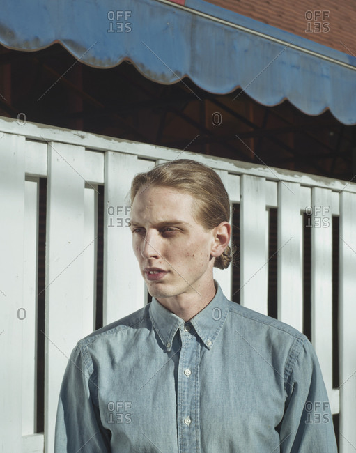Man with ponytail posing near fence
