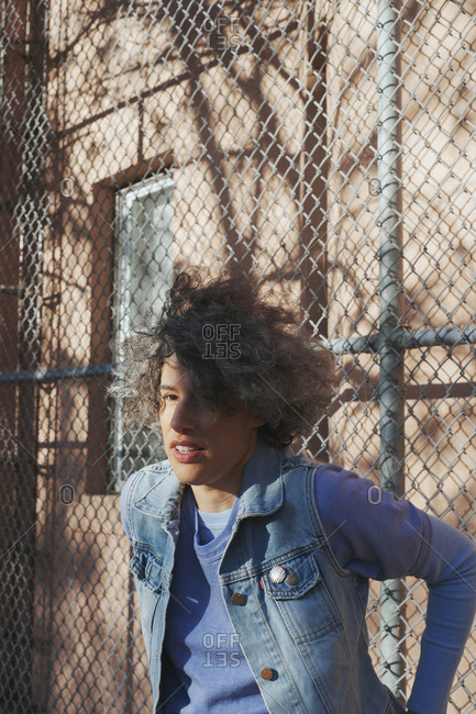 Woman with curly hair resting against fence