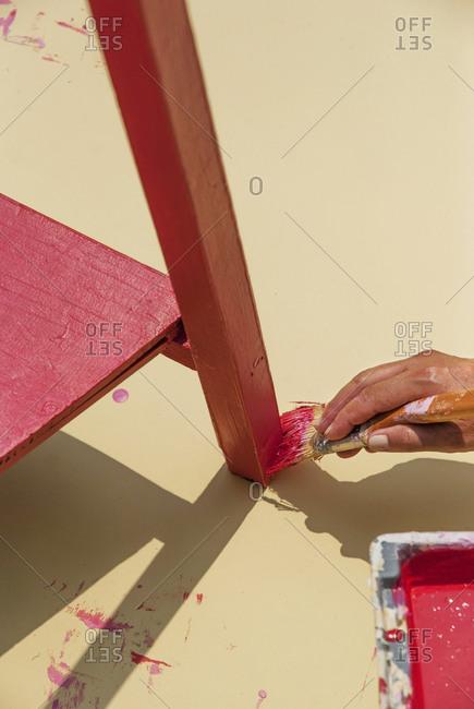 Woman painting leg of furniture