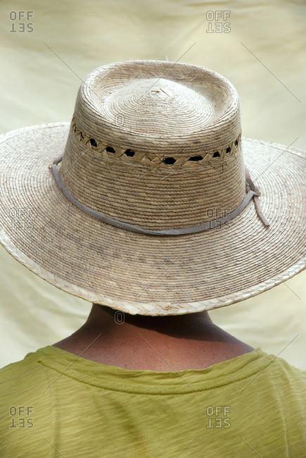 Person in straw hat from behind, studio shot