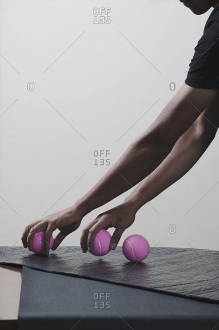Man arranging tennis balls, studio shot