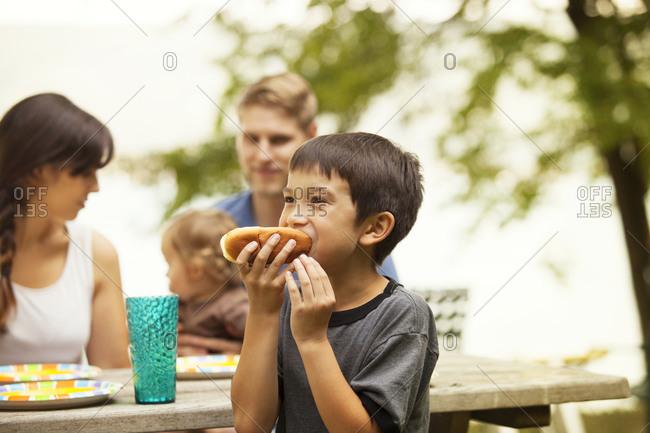 Boy eating a hot dog at a picnic table
