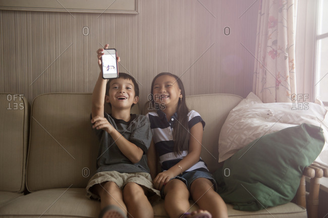 Two children looking at a smartphone on a couch