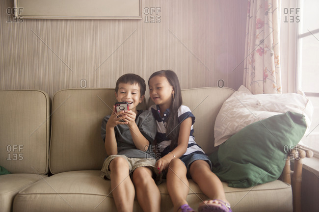 Children using a smartphone on a couch