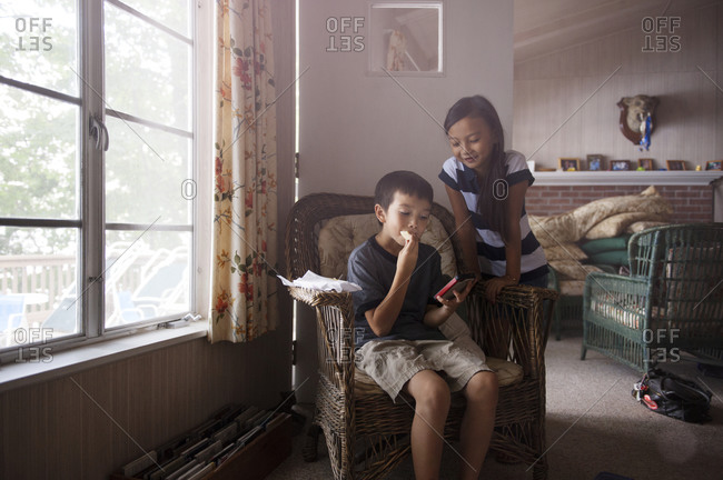 Children looking at a smartphone by the window