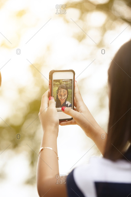 Young girl taking self portrait with a smartphone