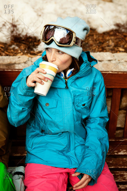 A woman sips coffee on a bench