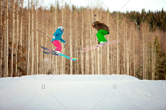 A couple skis off a jump together