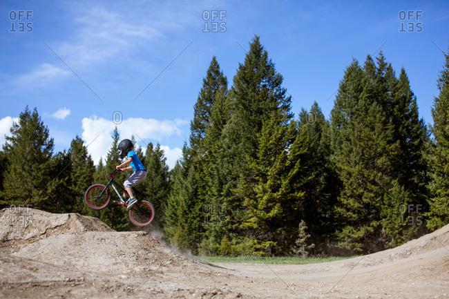 Young boy riding a bmx bike on a dirt track