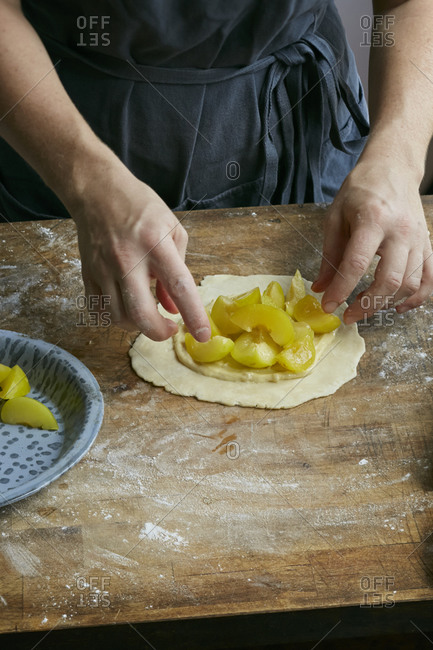Woman assembling peach tart