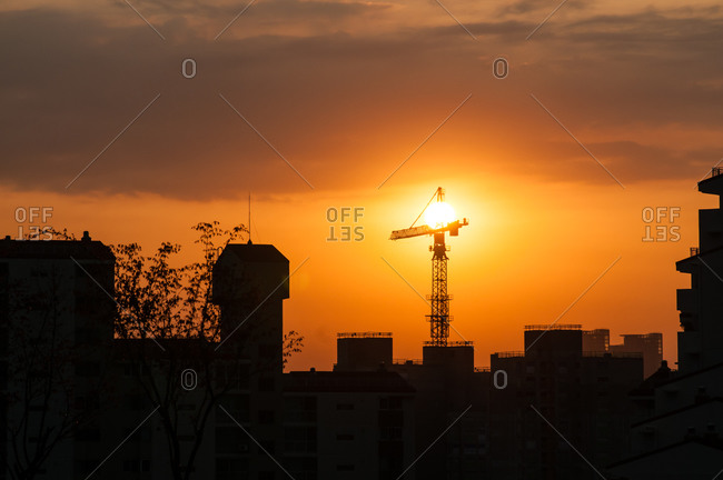 City skyline with crane at sunset