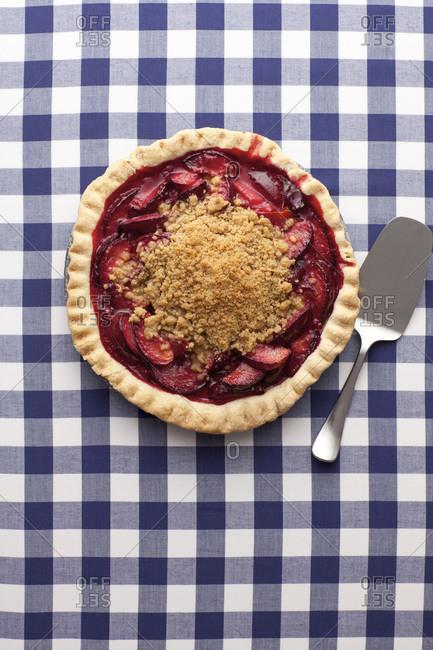Plum pie with a cake server